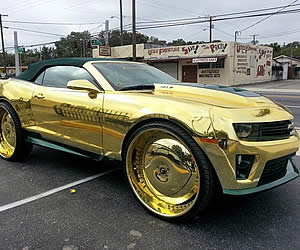 Gold Soaked King zl1 Camaro Rides on 30 inch Gilded Wheels with three 23 Inch TvsK